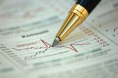 Goldene Feder, die Diagramm auf Finanzreport zeigt Stockbild