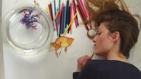 Goldene Fische des schönen weiblichen Künstlerabgehobenen betrages schließen oben auf Draufsicht stock video