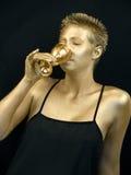 Goldene Frau, die von einem goldenen Becher trinkt Lizenzfreies Stockbild