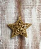 Goldene Funkeln-Stern-Weihnachtsverzierung auf hölzerner gemalter Tabelle Stockbild