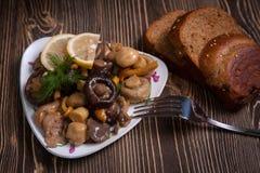 Goldene gebratene Pilze mit Zwiebeln, Zitrone, Brot Lizenzfreie Stockbilder