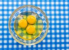 Goldene gelbe Eier knackten in Glasschüssel Stockfoto