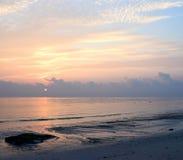 Goldene gelbe Linien in den Wolken im Morgen-Himmel mit aufgehende Sonne am Horizont über weitem Ozean lizenzfreie stockfotografie