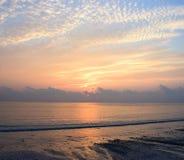 Goldene gelbe Linien in den Wolken im Morgen-Himmel mit aufgehende Sonne am Horizont über weitem Ozean stockbilder