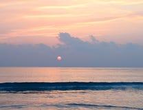 Goldene gelbe Linien im rosa Morgen-Himmel mit hellem aufgehende Sonne Horizont über Ozean mit Wellen stockfotografie