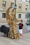 Goldene gemalte lebende Statue mit Flügeln und lächelndem Jungen an der Ramblas-Straße in Barcelona Stockfotografie