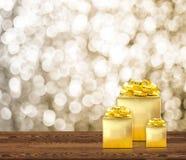 Goldene Geschenkbox auf hölzerne Tischplatte mit funkelndem bokeh Gold der Unschärfe Stockfotografie