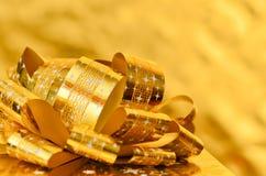 Goldene Geschenkbox mit Goldband Stockfoto