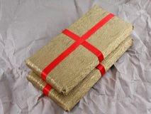 Goldene Geschenkbox mit rotem Bogen auf Weinleseschmutzpapier Stockfotos