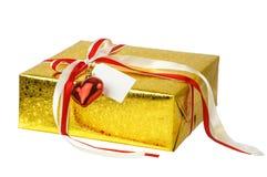Goldene Geschenkbox mit rotem Bogen und Karte lokalisiert auf Weiß Lizenzfreie Stockfotografie