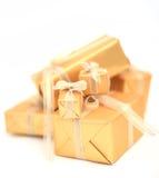 Goldene Geschenkboxen mit goldenem Band auf weißem Hintergrund Stockfotos