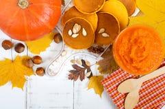 Goldene geschmackvolle nützliche Kürbispfannkuchen, Püree eines Kürbises auf einem weißen Hintergrund Lizenzfreie Stockfotos