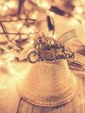 Goldene Glocke für Weihnachtsdekoration auf dunklem hölzernem Hintergrund I Lizenzfreie Stockfotografie