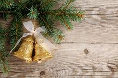 Goldene Glocken mit Bogen auf Holz Stockfotos