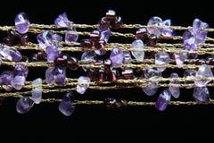 Goldene Halskette mit amethyst Steinen lizenzfreie stockbilder