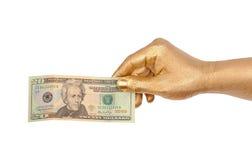 Goldene Hand mit einer Banknote. Lizenzfreies Stockfoto