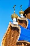 Goldene Hauben mit Kreuzen auf hölzerner orthodoxer Kirche gegen stockfotos