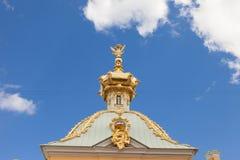 Goldene Hauben und Dekoration großartigen Palastes Peterhof gegen den hellen Himmel Stockbilder