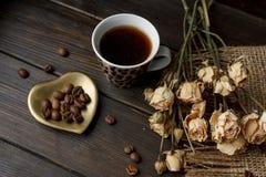 Goldene Herd-förmige Untertasse mit Röstkaffeebohnen Stockfotos