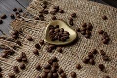 Goldene Herd-förmige Untertasse mit Röstkaffeebohnen Lizenzfreies Stockbild