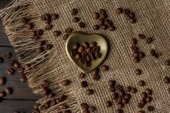 Goldene Herd-förmige Untertasse mit Röstkaffeebohnen Stockfoto