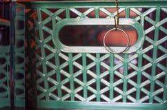 Goldene Hochzeit Ring Hanging auf einem Draht-Haken befestigt zum grünen Garderoben-Regal-Organisator Basket, mit Reflexionen im  lizenzfreie stockbilder