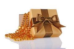 Goldene klassische glänzende offene Geschenkbox mit braunem Satinbogen und perlenbesetzter Girlande Stockfoto