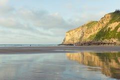 Goldene Klippen reflektiert im Wasser auf Strand Stockbilder