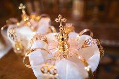 Goldene Krone der Nahaufnahme am Altar in der Kirche für die traditionelle religiöse Hochzeitszeremonie der Hochzeitspaare Lizenzfreie Stockfotos