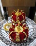 Goldene Kronen und ein Glas Wein für orthodoxe Hochzeit Stockfotografie