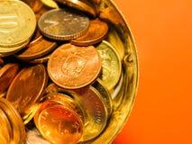Goldene Kupfer- und Silbermünzen in einer Schale mit orange Hintergrund Stockbilder