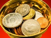 Goldene Kupfer- und Silbermünzen in einer Schale mit orange Hintergrund Lizenzfreie Stockbilder
