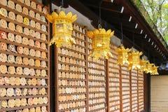 Goldene Laternen, die vor Spiegel-förmigem hölzernem preyer hängen Lizenzfreie Stockfotos