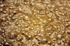 Goldene Luftblasen des Schmieröls Lizenzfreies Stockfoto