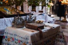 Goldene Luxuskronen mit Steinen für die Hochzeitszeremonie in der alten Kirche Lizenzfreie Stockfotos