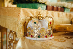 Goldene Luxuskronen mit Steinen für Hochzeitszeremonie in der alten Kirche Lizenzfreie Stockbilder