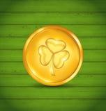 Goldene Münze mit Klee auf grüner hölzerner Beschaffenheit für St Patrick Stockbild