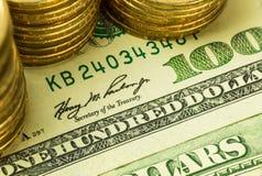 Goldene Münzen auf hundert Dollar Banknote Stockbild