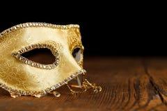 Goldene Maske auf Holztisch Stockbild