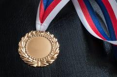 Goldene Medaille - Preis für einen Sieger auf schwarzem Hintergrund Stockbilder