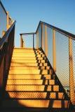 Goldene Metalltreppe in Richtung zum Dach unter blauem Himmel Lizenzfreie Stockfotos