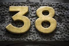 Goldene Nr. achtunddreißig auf dunkler Wand Stockbild