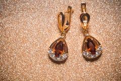 Goldene Ohrringe mit Granat stockbild