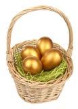 Goldene Ostereier im Korb getrennt lizenzfreie stockfotos