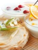 Goldene Pfannkuchen und zwei Fruchtjoghurt Stockbild
