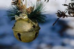 Goldene Pferdeschlitten-Bell-Weihnachtsverzierung, die einen Baum im Freien verziert Lizenzfreie Stockbilder