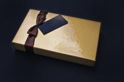 Goldene Pralinenschachtel geschlossen mit schwarzem Aufkleber Lizenzfreie Stockfotografie