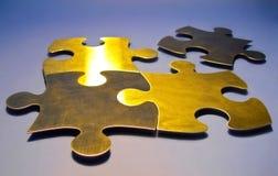 Goldene Puzzlespielstücke Lizenzfreie Stockfotografie