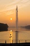 Goldene Reflexion eines Sonnenuntergangs auf Seeoberfläche vor künstlichem geysir auf Ada See in Belgrad Lizenzfreie Stockbilder