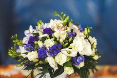 Goldene Ringe von Jungvermählten in einem weißen purpurroten Blumenstrauß, Nahaufnahme Stockbild